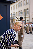 Young woman watching changing of the guard at Grand Ducal Palace, Luxembourg, Luxembourg