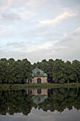 Historisches Gebäude und Bäume spiegeln sich im Wasser des Nymphenburger Kanal, München, Bayern, Deutschland