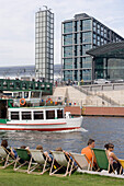 People relaxing in deckchairs at river Spree, Berlin Central Station in background, Berlin, Germany
