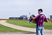 Young man wearing a football shirt playing accordiom, Berlin, Germany
