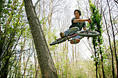 Young man doing a jump on his BMX in the woods, Mindelheim, Bavaria, Germany