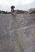 Mountainbiker balanciert am Rand einer Schlucht, Kaufbeuren, Bayern, Deutschland