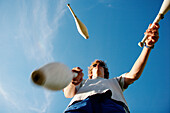 Young man juggling with clubs, Irsee, Bavaria, Germany