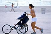 Woman with pushchair on beach, South Beach, Miami, Florida, USA