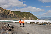 Two Hikers on the Red Rocks Coastal Walk, Owhiro Bay, near Wellington, North Island, New Zealand