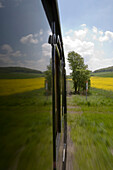 View out of a window from Excursion Train, Rhoen-Zuegle between Fladungen and Ostheim, Rhoen, Bavaria, Germany