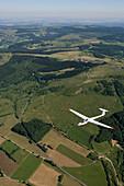 Aerial photo of a glider airplane over Rhoen Region, Near Wasserkuppe Mountain, Rhoen, Hesse, Germany