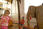 Child, girl with toy elefant and monkey in the toy museum in Sonneberg, Thuringia, Germany