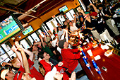People cheering in Cask and Flagon Sports Bar, Fenway Park, Boston, Massachusetts, USA