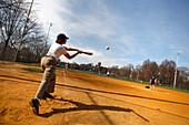 A woman playing softball on Boston Common, Boston, Massachusetts, USA