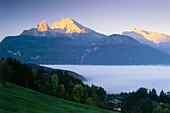 View over valley with fog to Watzmann and Hochkalter peaks, Schoenau am Koenigssee (King's Lake), Berchtesgadener Land, Bavaria, Germany