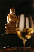 Buddha statue and a white wine glass