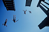 Four people juming from diving platform into water, Lake Ammer, Bavaria, Germany