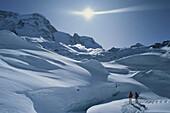 Skiers, avalanche in background, Schwarztorgletscher, Zermatt, Switzerland