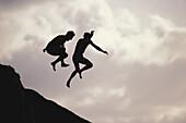 Men jumping in the water, Sunset Beach, Oahu, Hawaii, USA