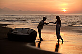 A young woman being offered a drink from a waiter on the beach at sunset, near Uluwatu, Bali, Indonesia