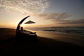 A young woman having a rest on a sun lounger on the beach at sunset, near Uluwatu, Bali, Indonesia