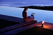 Young woman sitting with laptop at the edge of a swimming pool, looking at photographs, near Uluwatu, Bali, Indonesia