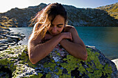 Young woman leaning on rock at lake Laghi d'Orsirora, Gotthard, Canton of Ticino, Switzerland