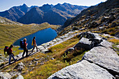 Three young people hiking, Lago d'Orsino, Gotthard, Canton of Ticino, Switzerland