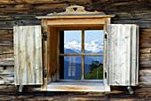 Reflection of snow covered mountains in alpine hut window, Wilder Kaiser range, Kaiser range, Tyrol, Austria