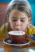 Girl (5 years) looking at cup of dekorated cappuccino served in a cafe, Bremen, Germany
