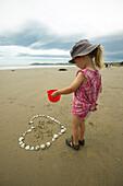 Girl exploring heart made from seashells, beach at the Moeraki Boulders, south of Oamaru, Eastcoast, South Island, New Zealand