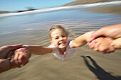 Girl (5 y.) turning around her father (flying merry go round), at Okains Bay, Bank`s Peninsula, east coast, South Island, New Zealand