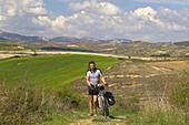 Landscape with pilgrim pushing bike, near Viana, Navarra, Spain