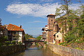 Old stone bridge over the river Nive with church in the background, St. James Way, St. Jean-Pied-de-Port, Pyrenees, Dep. Pyrénées-Atlantiques, France