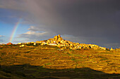 Landscape with rainbow and dramatic sky after a thunderstorm, small town on top of a mountain, UjueLands, Navarra, Spain