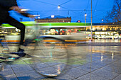 Tram and cyclist passing railway station forecourt, Hanover central station, Lower Saxony, Germany