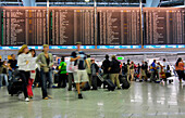 Travellers waiting at the flight information board, Frankfurt Airport, Hesse, Germany