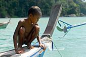 Child, boy, crouching on a boat, Chao Naam, Moken, Surin Islands Marine National Park, Ko Surin Noi, Phang Nga, Thailand