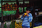 Fruit Stall selling fruit, Boy eating a fruit, Garganta do Registro, Serra da Mantiqueira, Minas Gerais, Brasil, South America