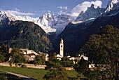 Das Bergdorf Soglio vor verschneiten Gipfeln der Scioragruppe, Bergell, Graubünden, Schweiz
