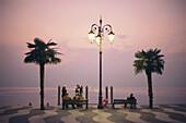 Menschen sitzen abends auf einer Bank der Uferpromenade am Gardasee, Lazise, Provinz Verona, Veneto, Italien