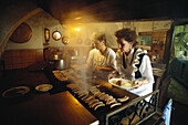 Two female cooks inside the Historical Sausage Kitchen, Historische Wurstküche, Regensburg, Bavaria, Germany