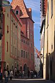Mittelalterliche Häuser säumen eine belebte Gasse in Regensburg, Oberpfalz, Bayern, Deutschland
