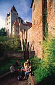 Junge Leute machen Picknick unter mächtigen Mauern und dem Wittelsbacher Turm der Burg Trausnitz, Landshut, Niederbayern, Bayern, Deutschland