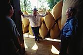 Ein Hopfenbauer spricht mit Arbeitern bei der Anlieferung von Säcken mit Hopfen, Hallertau, Niederbayern, Bayern, Deutschland