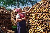 Bäuerin mit Kopftuch und Schürze schichtet Brennholz zu kunstvollem Holzstoss, Wiesenfelden, Bayerischer Wald, Niederbayern, Bayern, Deutschland