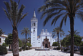 Whitewashed church of Saint John Baptist with palm trees and fountain on main square, La Palma del Condado, Huelva province, Costa de la Luz, Andalusia, Spain
