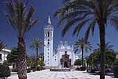 Weißgekalkte Kirche Iglesia de San Juan Bautista mit Palmen und Brunnen auf der Plaza Mayor, La Palma del Condado, Provinz Huelva,Costa de la Luz, Andalusien, Spanien