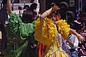 Junge Frauen in bunten Rüschenkleidern tanzen Flamenco, Jerez de la Frontera, Provinz Cádiz, Andalusien. Spanien