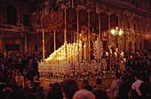 Menschen tragen am Abend eine tonnenschwere, mit Kerzen geschmückte Marienstatue zur Kathedrale, Plaza San Francisco, Sevilla, Andalusien. Spanien