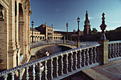Delicate bridges with ceramic balustrades over canal with rowing boats at the Palacio Central, Seville, Andalusia, Spain