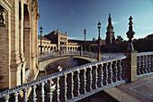 Zierliche Brücken mit Geländern aus blau glasierter Keramik über Kanal mit Ruderbooten am Palacio Central, Sevilla, Andalusien. Spanien