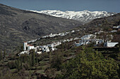Two white villages Bubión and Capileira in the Alpujarras valley beneath the snow covered mountain range Sierra Nevada, Granada province, Andalusia, Spain