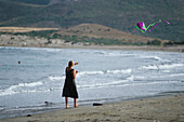 Girl flying a kite on the beach, Playa de los Genoveses, Parque Natural Cabo de Gata, Andalusia, Spain